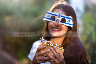 Israel's Independence Day; Israeli girl holding pita with falafel