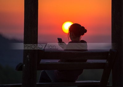 Girl with cellphone at sunset