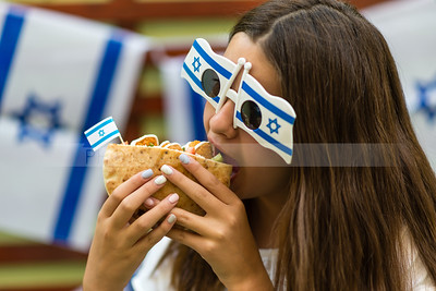 Israeli girl eating pita with falafel; Israel's Independence Day