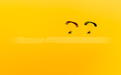Two paragliders in a sunset sky