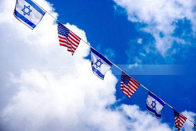 American and Israeli flags against a cloudy sky