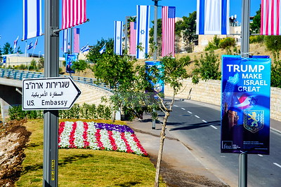 Street sign on a road towards a new US embassy in Jerusalem, adorned with American and Israeli flags