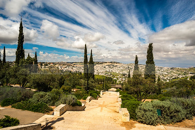 Stairs of a promenade, with clouds over Jerusalem and the Mount of Olives in the background