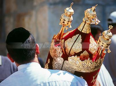 Jewish man in black kippah carrying a Torah scroll - Jewish traditions