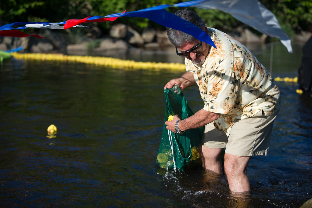 . Fitchburg Mayor Stephen DiNatale digs rubber ducks out of the river alongside Fitchburg firefighters during Sunday\'s duck race at Riverfront Park in Fitchburg on July 9, 2017.  SENTINEL & ENTERPRISE JEFF PORTER