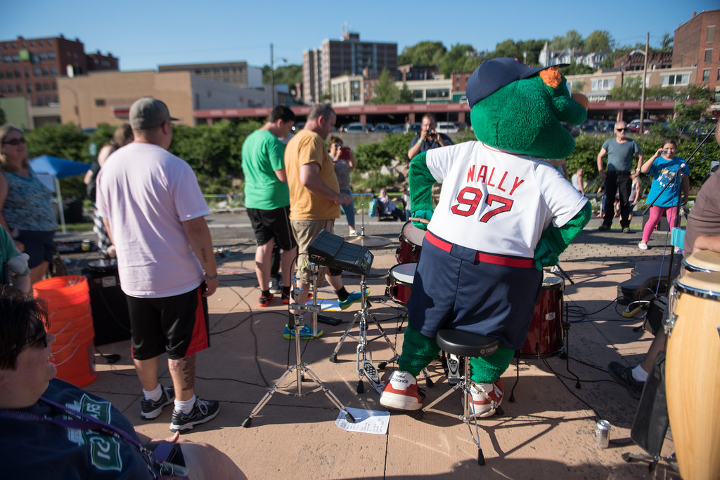 """. Boston Red Sox mascot \""""Wally the Green Giant\"""" taunts a band member for a drum battle during Sunday\'s duck race at Riverfront Park in Fitchburg on July 9, 2017.  SENTINEL & ENTERPRISE JEFF PORTER"""
