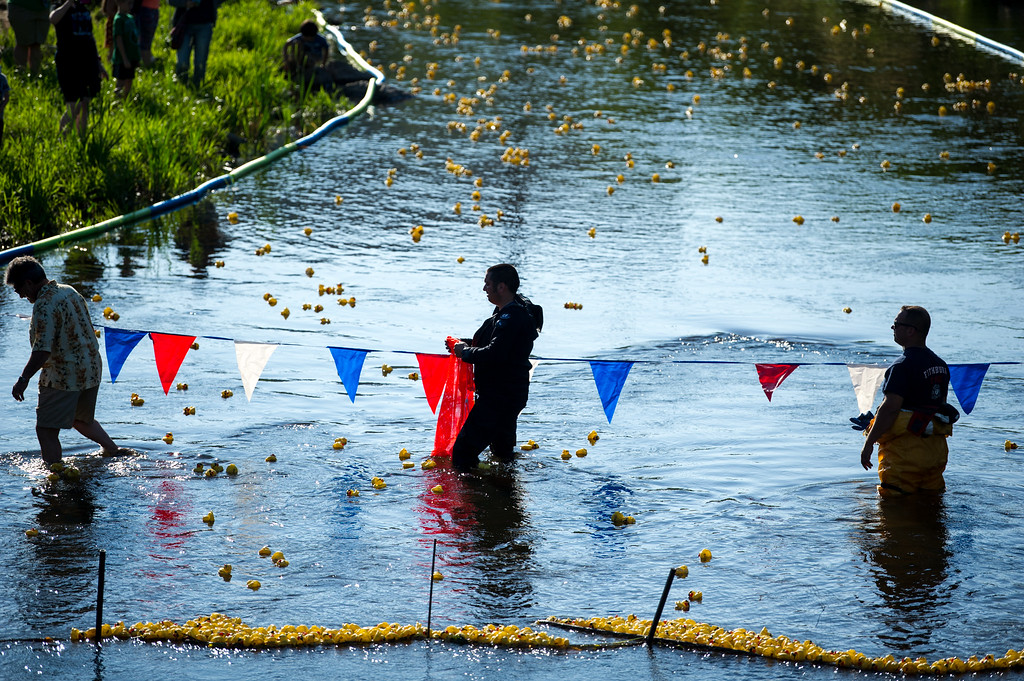 . Fitchburg Mayor Stephen DiNatale (left) digs rubber ducks out of the river alongside Fitchburg firefighters during Sunday\'s duck race at Riverfront Park in Fitchburg on July 9, 2017.  SENTINEL & ENTERPRISE JEFF PORTER