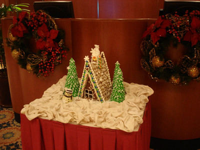 Gingerbread house next to podium in dining room entrance