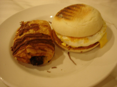 International cafe breakfast: English muffin egg sandwich and chocolate filled pastry