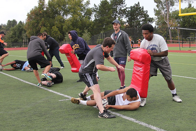Coach Vic Dippenaar analyzes technique as Mark Qoro holds the rucking bag and Eduardo Zentano presents the ball with a jackknife movement during the rucking drill of the new 2012 season on Sat 10-29-11.