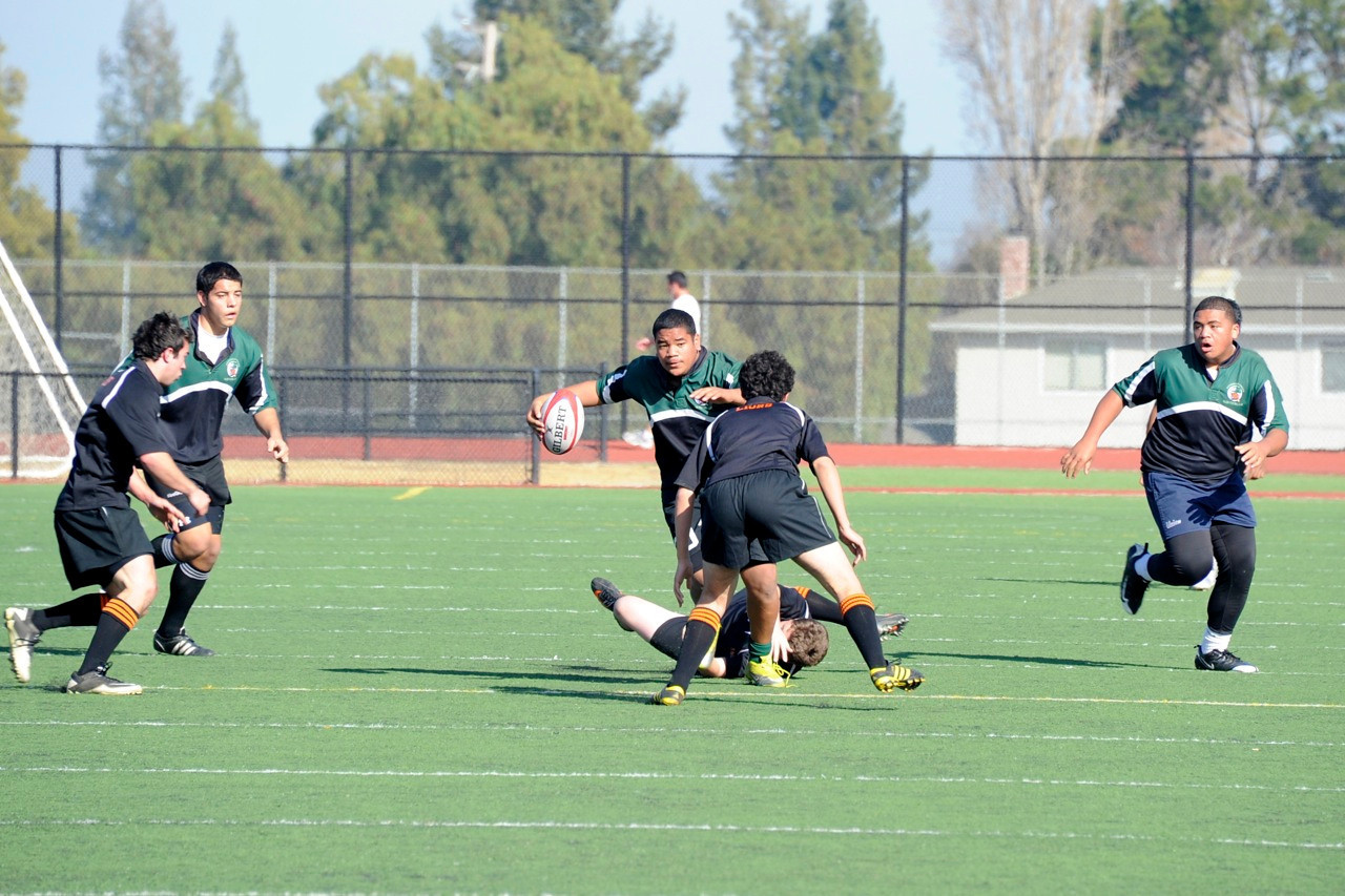 2012 Peninsula Green Rugby vs Los Gatos Lions 01-14-12: Kolo Vaimau carries the ball forward  as Los Gatos defenders attempt to tackle him as Sam Vaimau and Juan Cervantes offer support on both sides. (026)