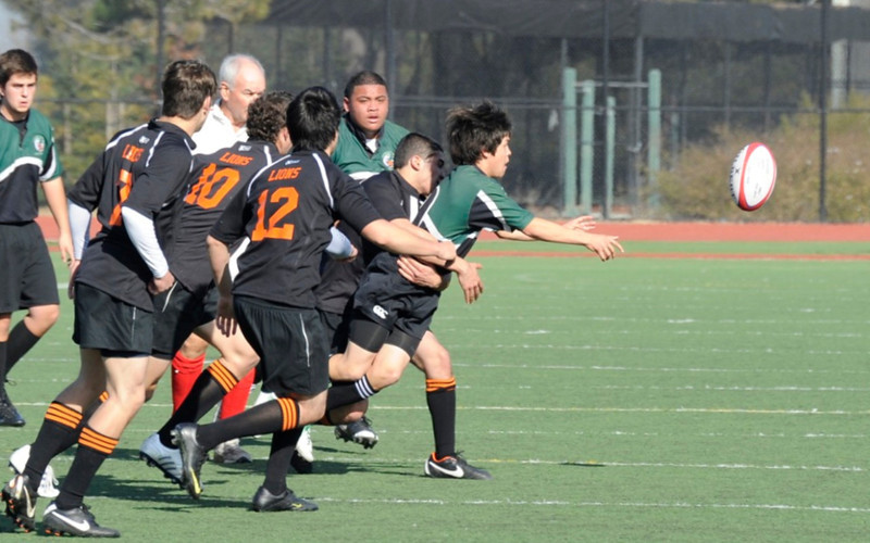 2012 Peninsula Green Rugby vs Los Gatos Lions 01-14-12: Erick Cortinas gets the ball out to the backs while under pressure from the Los Gatos defenders as Sam Vaimau closes in for support (017) edit