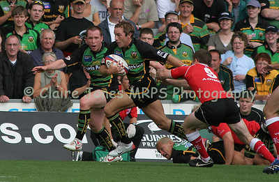 Will Harries evades the tackle by Greg Nicholls, encouraged by Paul Diggin
