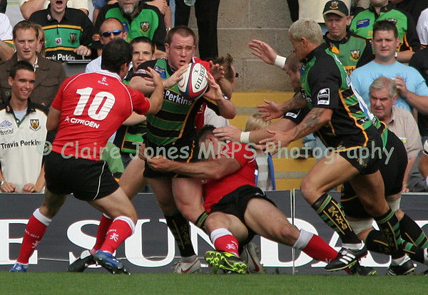 Paul Diggin tackled by Greg Evans, attempts a pass to Carlos Spencer. Gareth Morgan attempts a block.