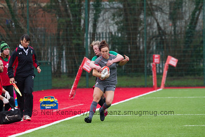 Bethan Dainton with the ball is tackled by Elise O'Byrne White