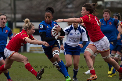 Romane Menager with the ball about to be double tackled by Elinore Snowsill and Sioned Harries