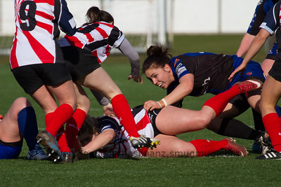 Charlie Murray (Dragons) looks for the ball at the breakdown as Elli Norkett places it back