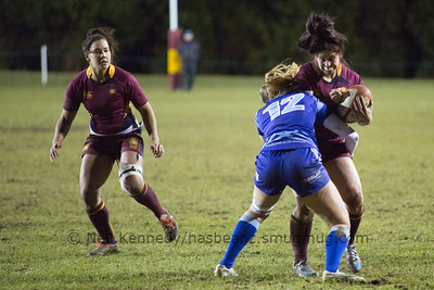 Daisie Mayes with the ball is tackled by Sarah Bern
