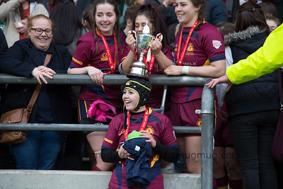 Chloe Davies, Daise Mayes and Sam Morris balance the cup on Amberly Ruck's head