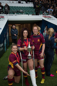 Meg Daley and Bronnie Jones support Daisie Mayes holding the cup she broke her leg earning