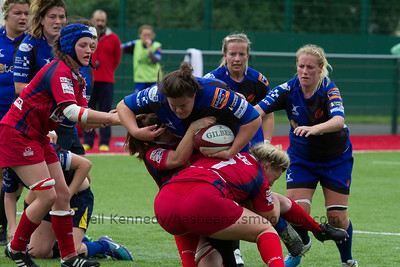 Kate Hallett, with the ball, is being doiuble tackled