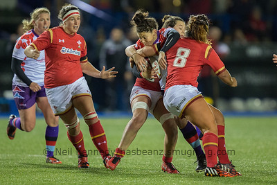 Gemma Rowland seeks a way through the tackles of Sioned Harries and Shona Powell-Hughes