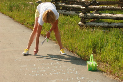 Jancie Hugues writes the names of all runners on the sidewalk approaching the finish line - one very backbreaking job.