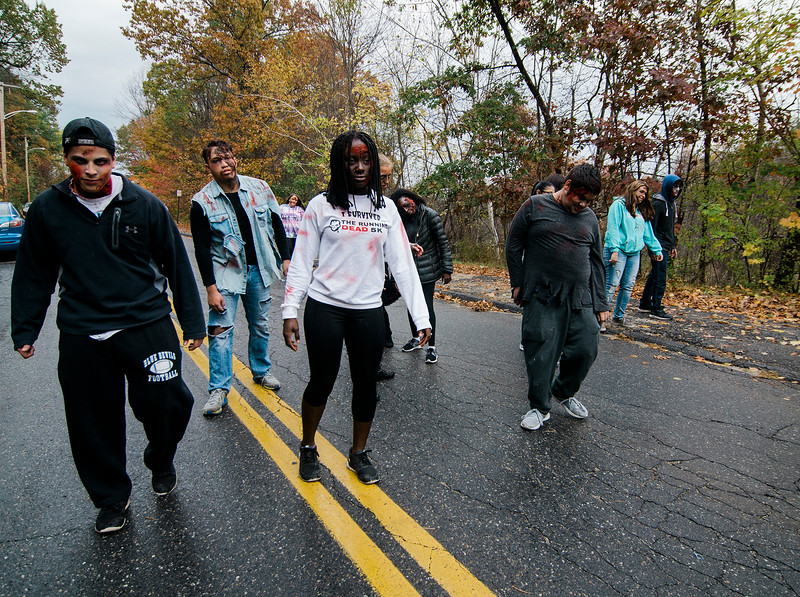 "Leominster High ""zombies"" approach passing runners during the Running Dead 5K on Saturday afternoon. The Class of 2018 held the event in hopes of reaching their target revenue goal of $2,000. The money will be used to help cover graduation, prom and class gift costs. SENTINEL & ENTERPRISE / Ashley Green"