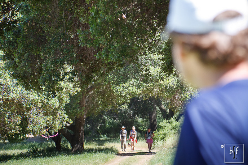 An onlooker sees a couple of hikers and a runner making her way to the finish.