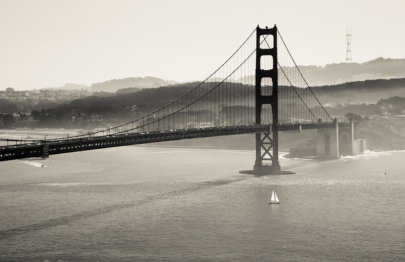 A sailboat travels underneath the south end of the Golden Gate.