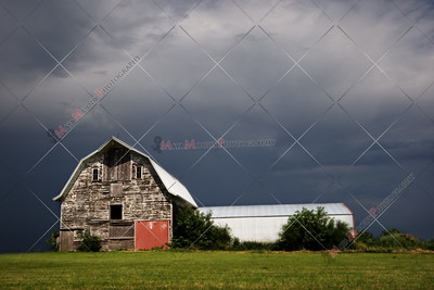 Weathered Illinois farm house with stormy sky