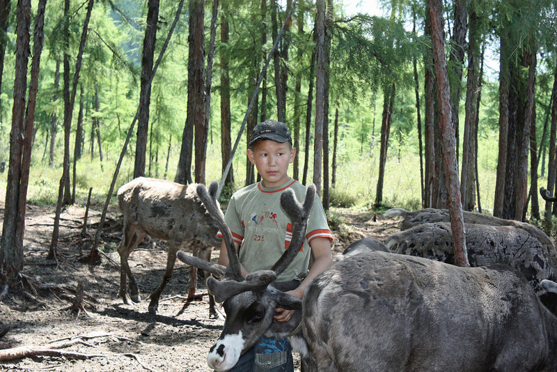 Young Evenk boy with his reindeer.