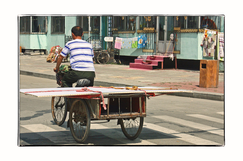 Transporting a sheet of drywall in Heihe, China.