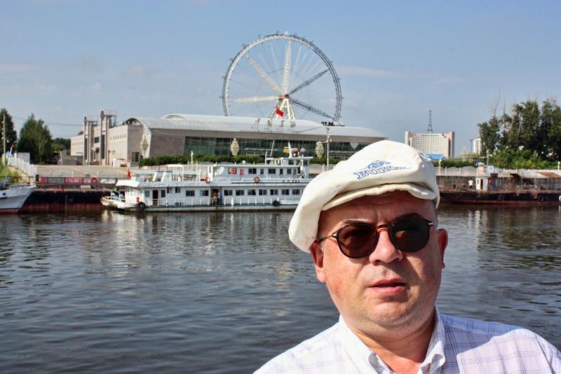 Petrov waiting to cross to the other side.<br /> <br /> За спиной Дмитрия Петрова - колесо обозрения в Хайхэ. Китайцы делают  колесо в 80 метров, раза эдак в 4 больше благовещенского.