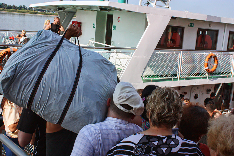 Dima gets hit in the face as the crowds board the ferry to Heihe, China.