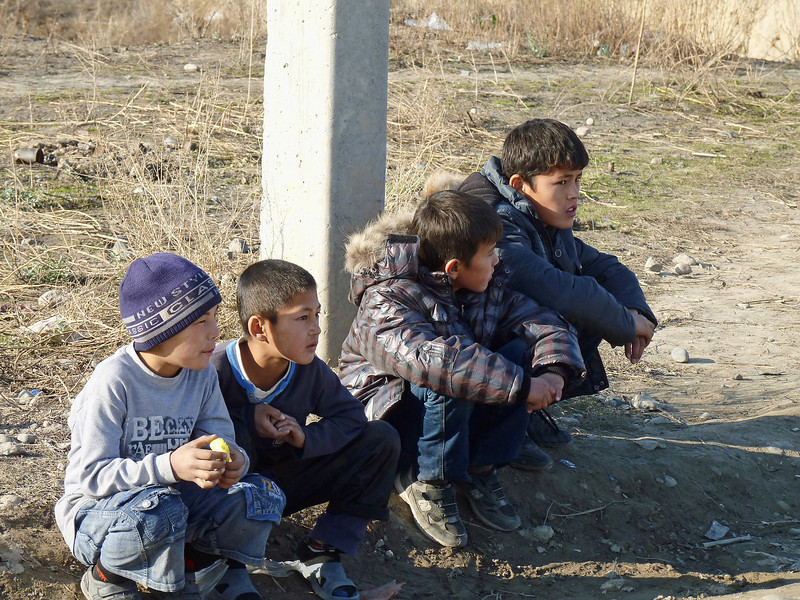 Boys sitting by the side of the road.