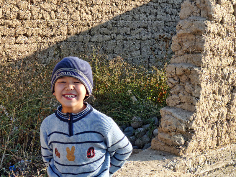 Happy kid. Stones, mud & hay are the primary building materials.