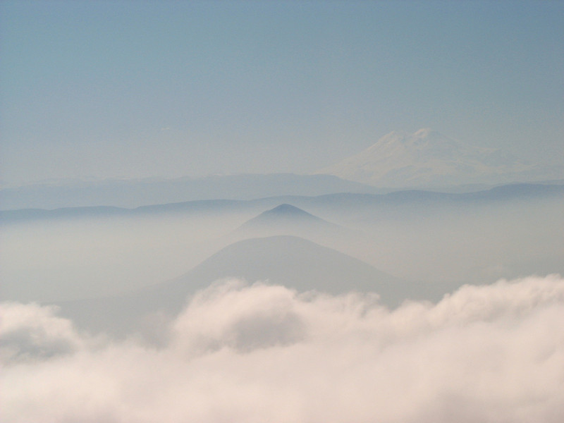 Blue mountains in the fog including Mt. Elbrus, Europe's tallest mountain, in the distance.