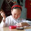 Маленькая девочка эвенка Вика вышивает бисером.