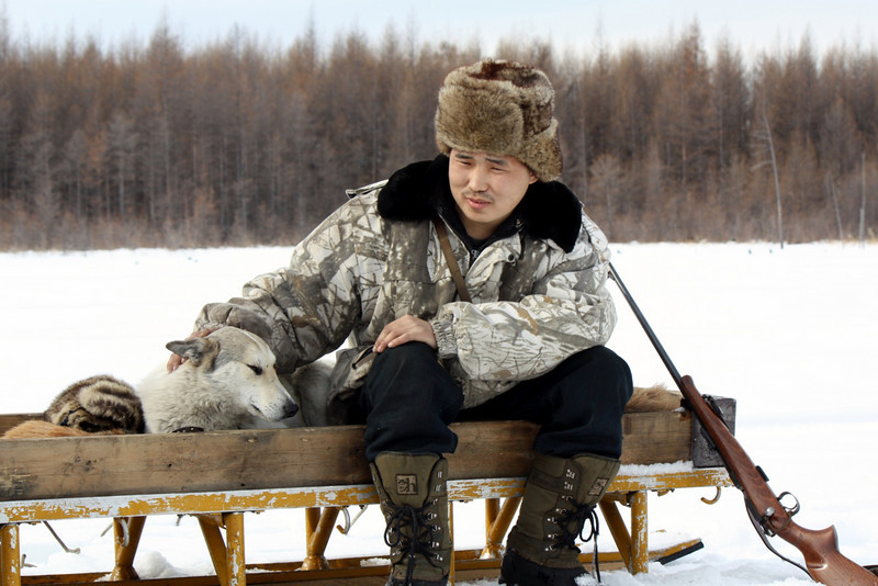Evenk man & his dog taking a break from hunting outside the village of Chapo-Ologo in the Kalar area of the Transbaikal Region of Siberia.