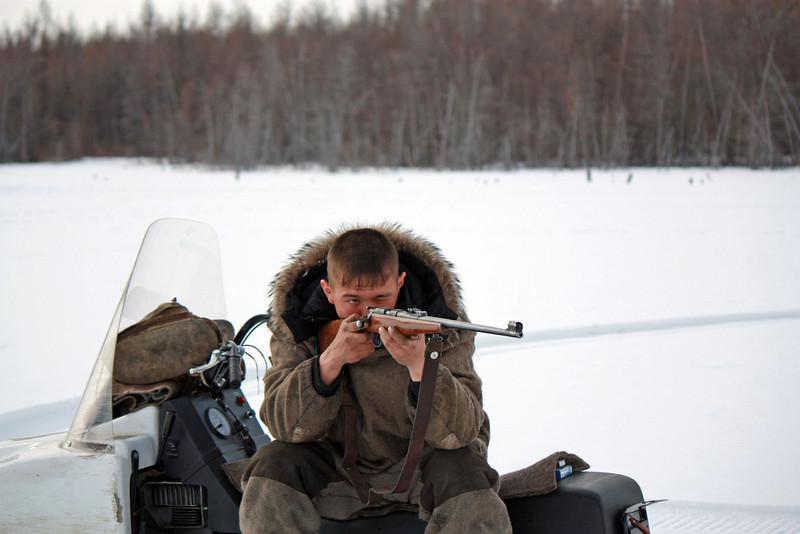 Эвенк на льду озера целится. Каларский район.