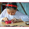 Red headband. Evenk girl concentrating on her bead work while making traditional Evenk amulets.