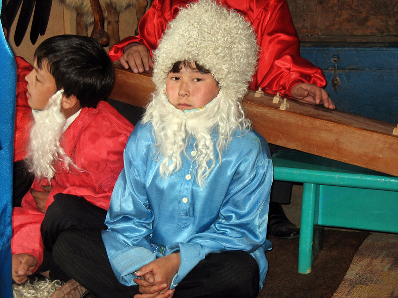 Boy dressed as a village elder watching the wedding ceremony.