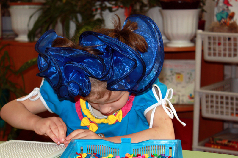 A blind girl with a bow in her hair.