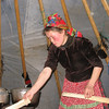 Nenets woman, Sveta, firing up the stove in her chum (tent).
