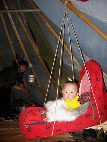The baby swings while the parents work.