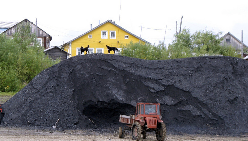Dogs on a coal pile as seen from the river. Before the oil boom hit, the Nenets Autonomous District was a major source of coal.