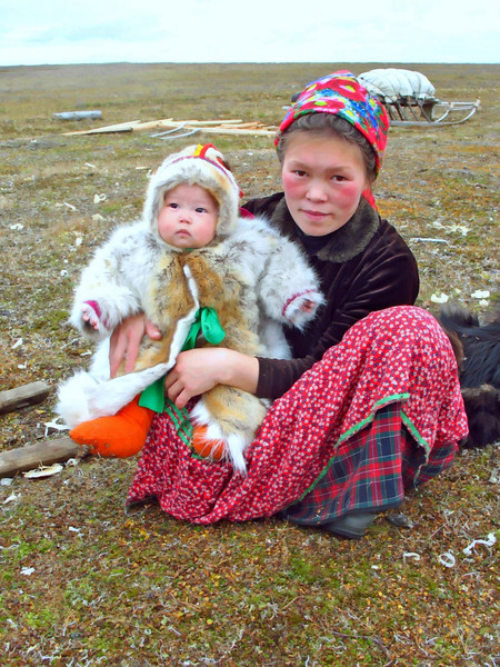 Nenets mother, Sveta, with her baby bundled in fur on the tundra. (09.08.2009)