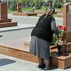 Grandmother arranging flowers on the grave of a beloved one. (Crop)