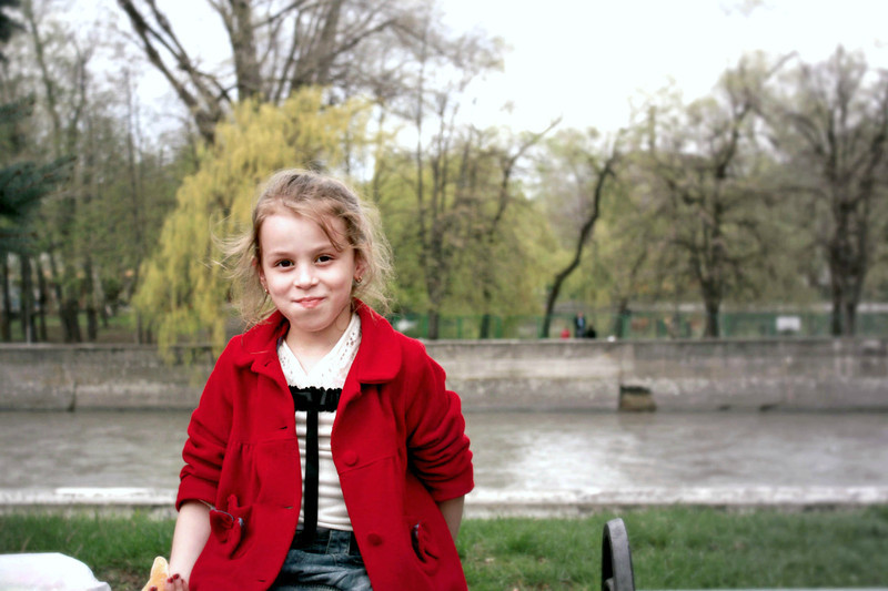 Girl eating an orange in the park.